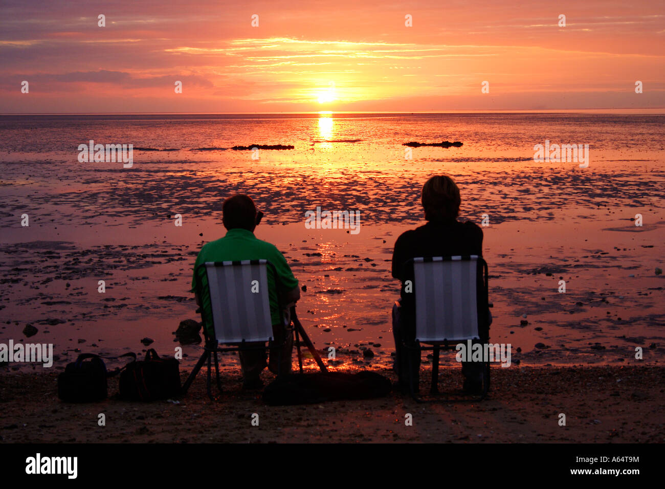 two people sitting on chairs watching a glorious sunset at Snettisham beach, West Norfolk coast, UK - Stock Image