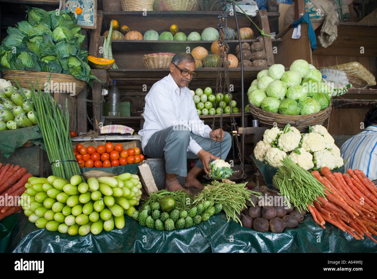 A man selling vegetables at Crawford Market in Mumbai India - Stock Image