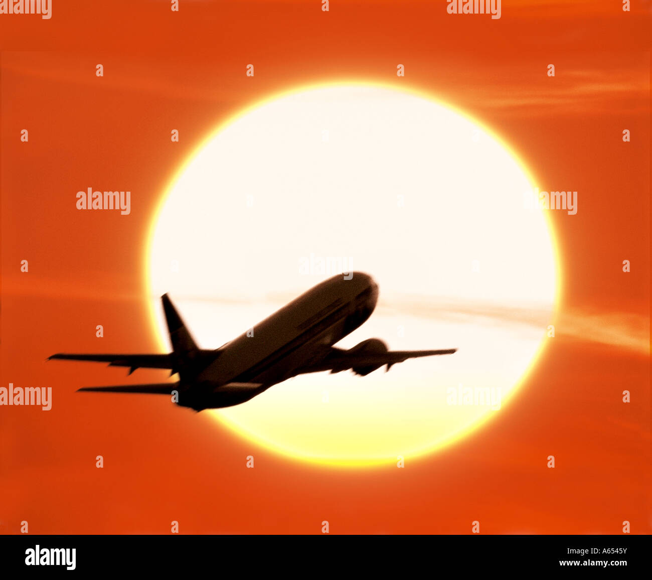 Plane taking off silhouetted against the setting sun - Stock Image