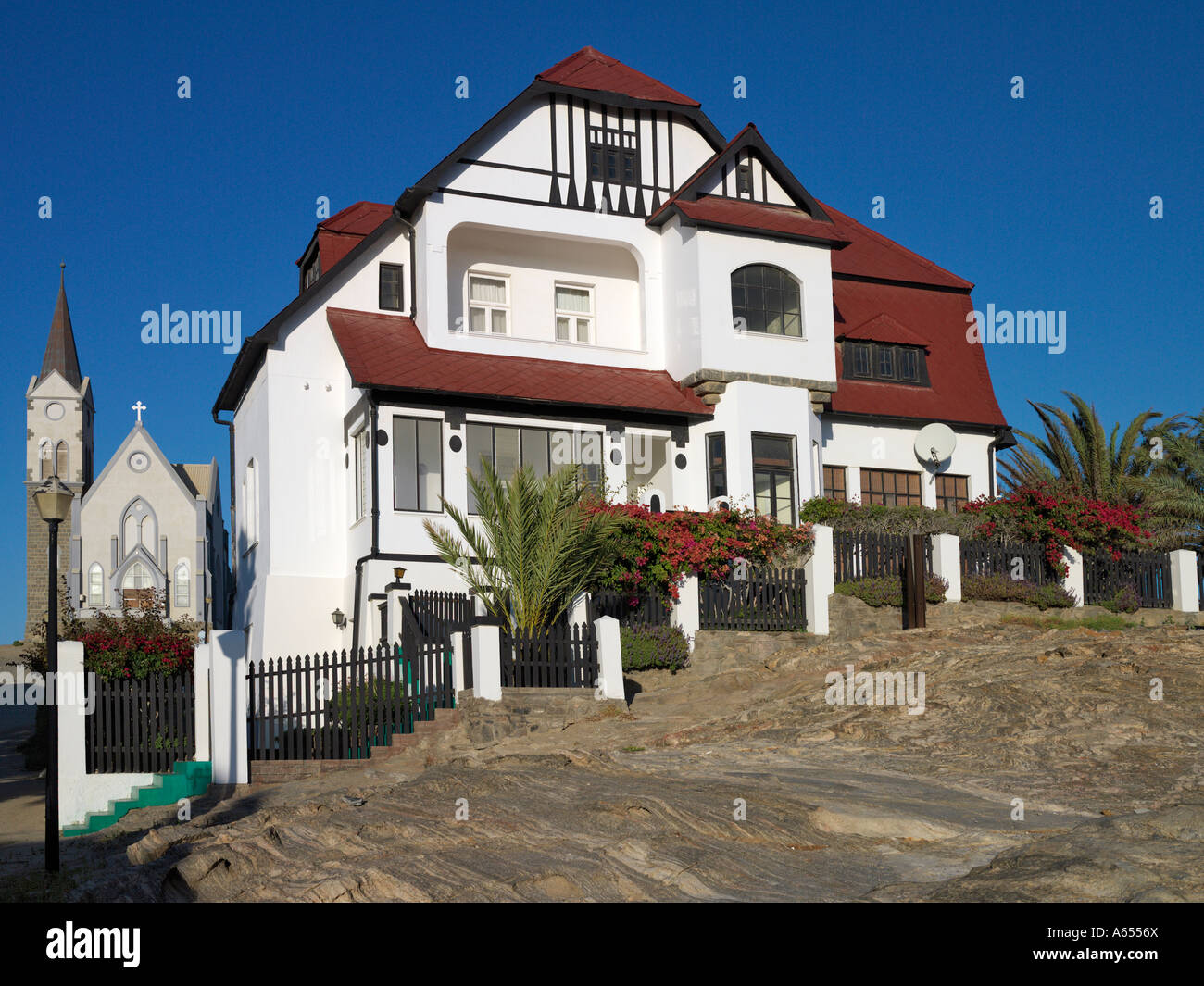 A Well Preserved German Colonial House In Luderitz With The Towns Main Lutheran Church Background