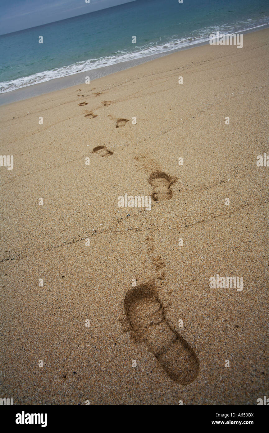 Footprints in the Sand on a beach disappearing into the Sea - Stock Image