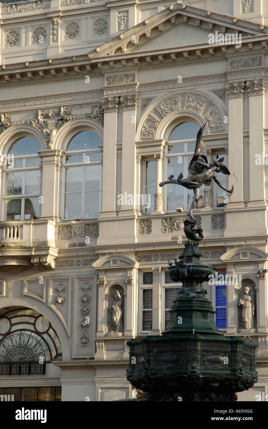 Statue of Eros seen against the architecture of ornate white Victorian buildings in Piccadilly Circus London England - Stock Image