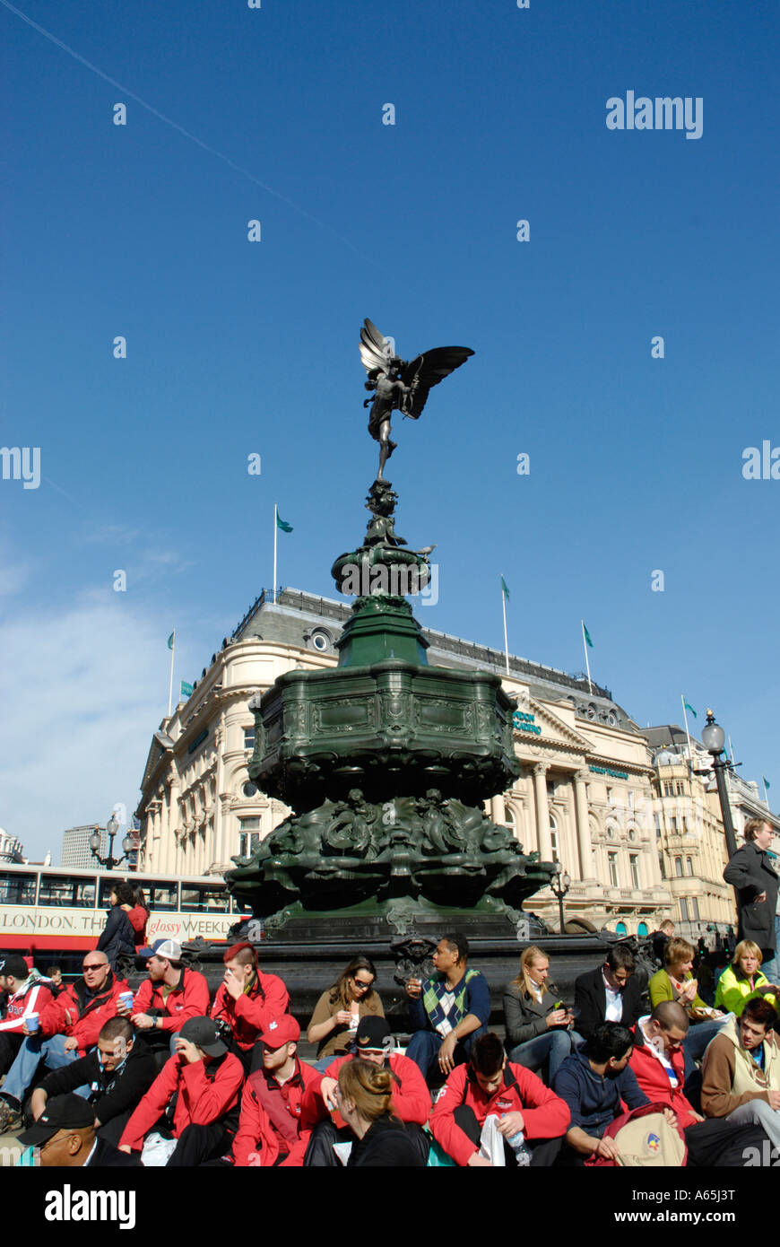 Tourists in bright red colored jackets sitting under the Statue of Eros, Piccadilly Circus, London, England, UK - Stock Image
