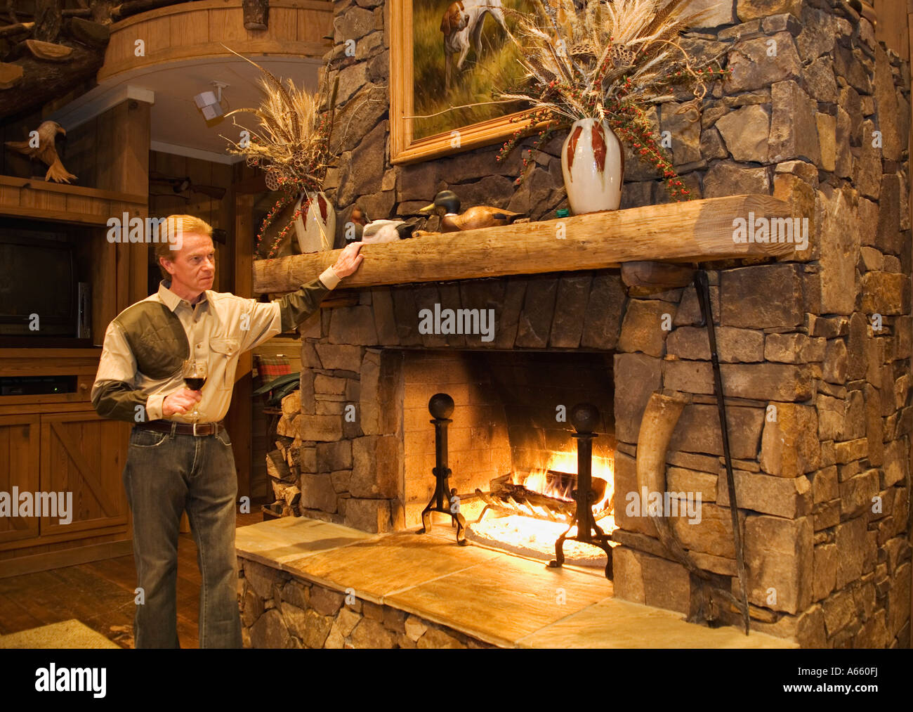 Man Relaxing Beside Fireplace In Lodge With Glass Of Wine After A Day Quail Hunting Buckeye Plantation Georgia