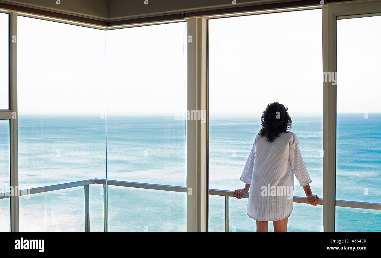 Woman looking at view, standing on balcony, back view - Stock Image