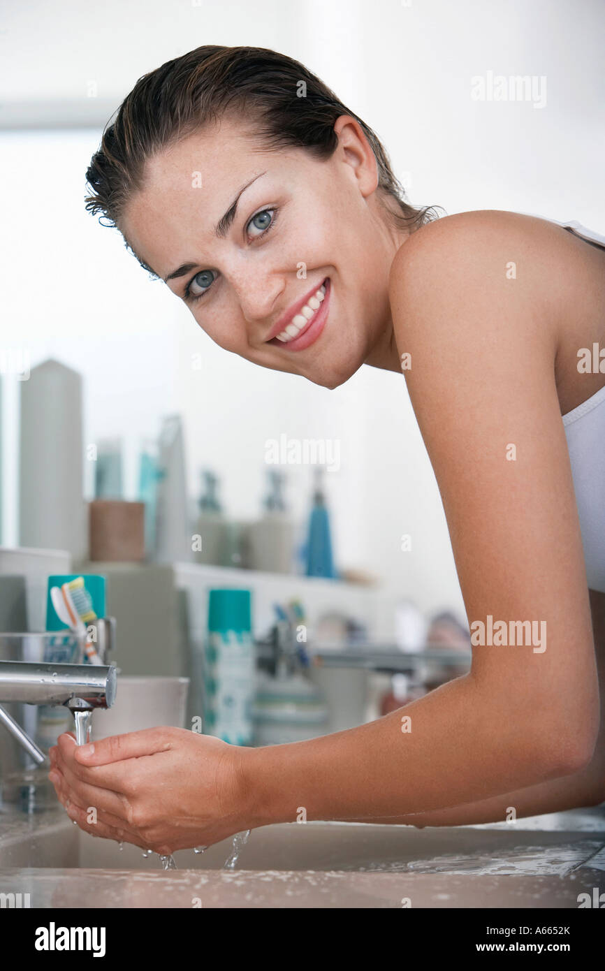 Woman washing face in bathroom - Stock Image