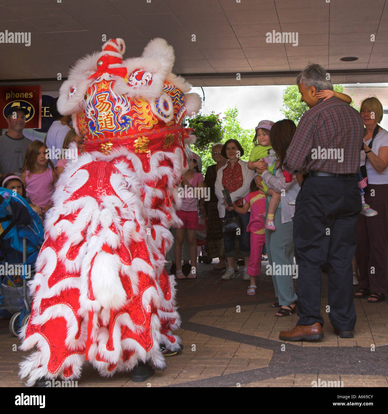 Malaysian Lion Dance entertaining children and shoppers - Stock Image