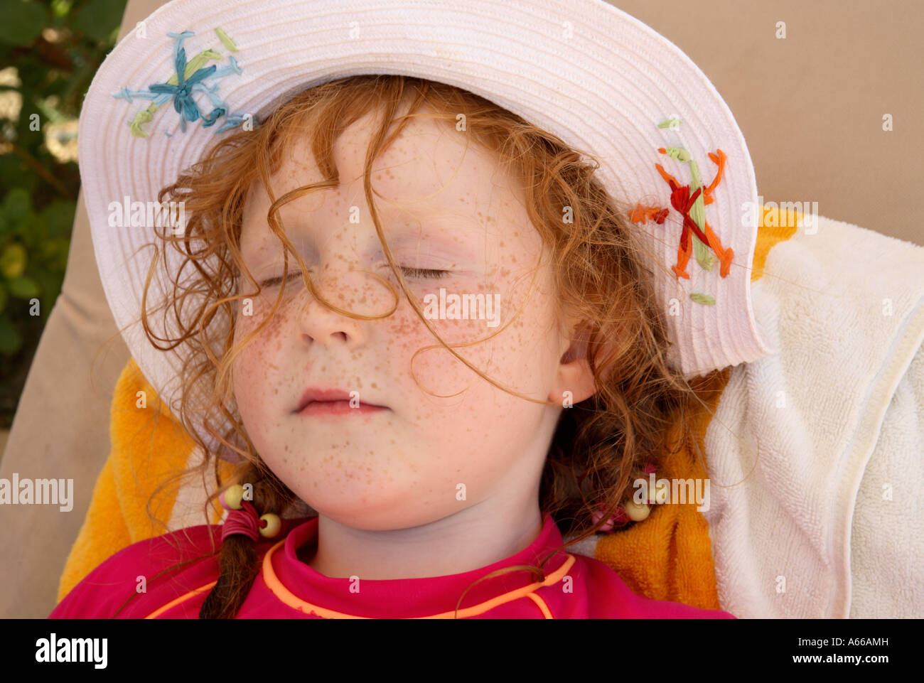 062d68c2c a small girl with red hair sleeping wearing a sun hat Stock Photo ...
