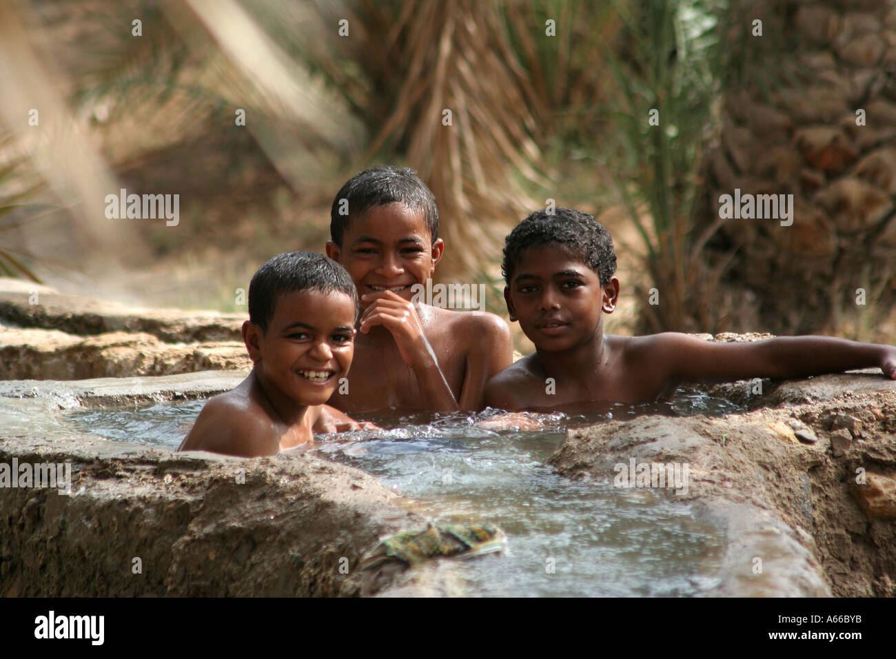Local boys cooling off in the waters of the falaj or irrigation canal in Sur, Oman - Stock Image