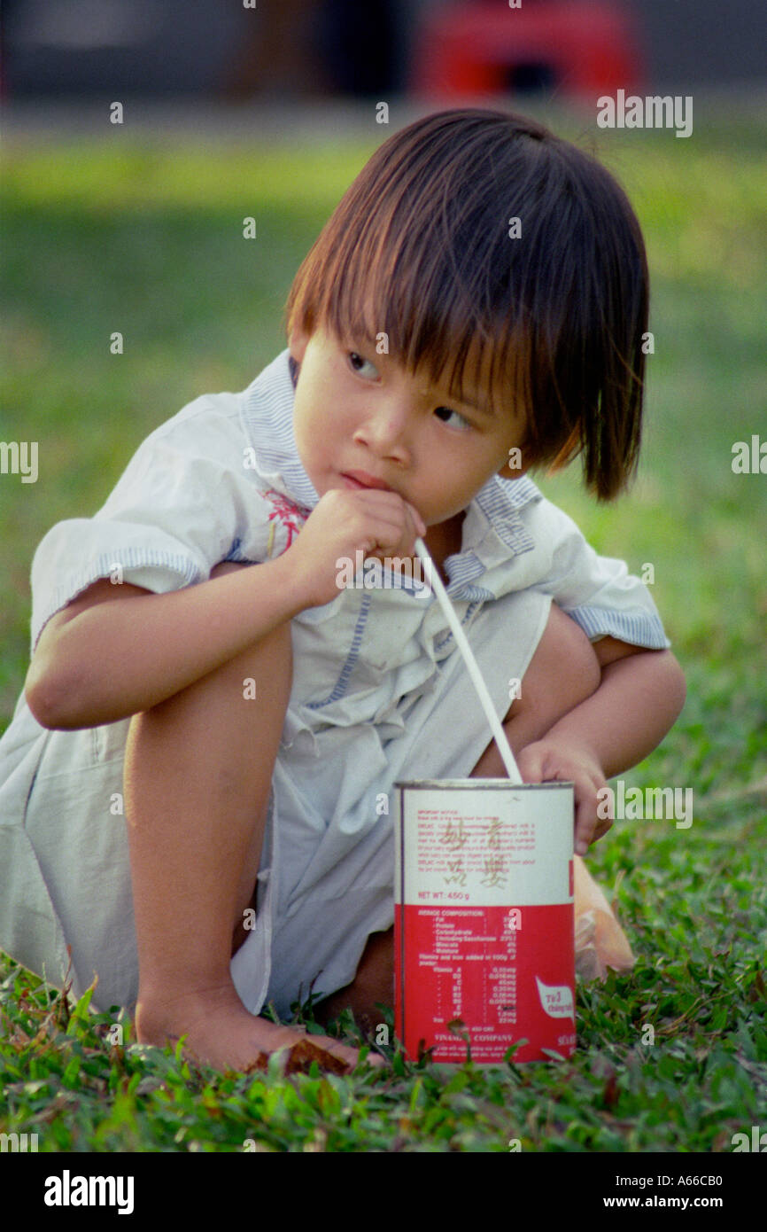 Young Vietnamese girl takes a sip from a milk can in Ho Chi Minh City Vietnam Stock Photo