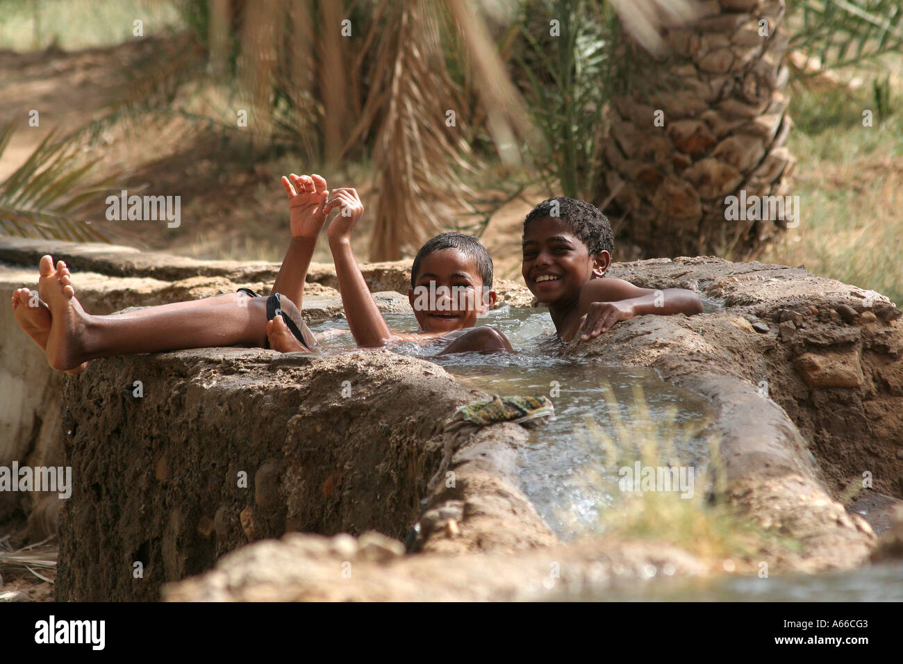 Local boys playing in the waters of the falaj or irrigation ditch in Sur, Oman - Stock Image