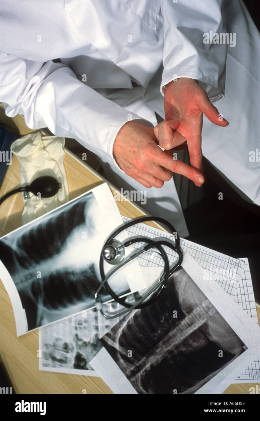 Doctor in surgery with chest Xrays and stethoscope on the desk discusses medical treatment option hands only - Stock Image