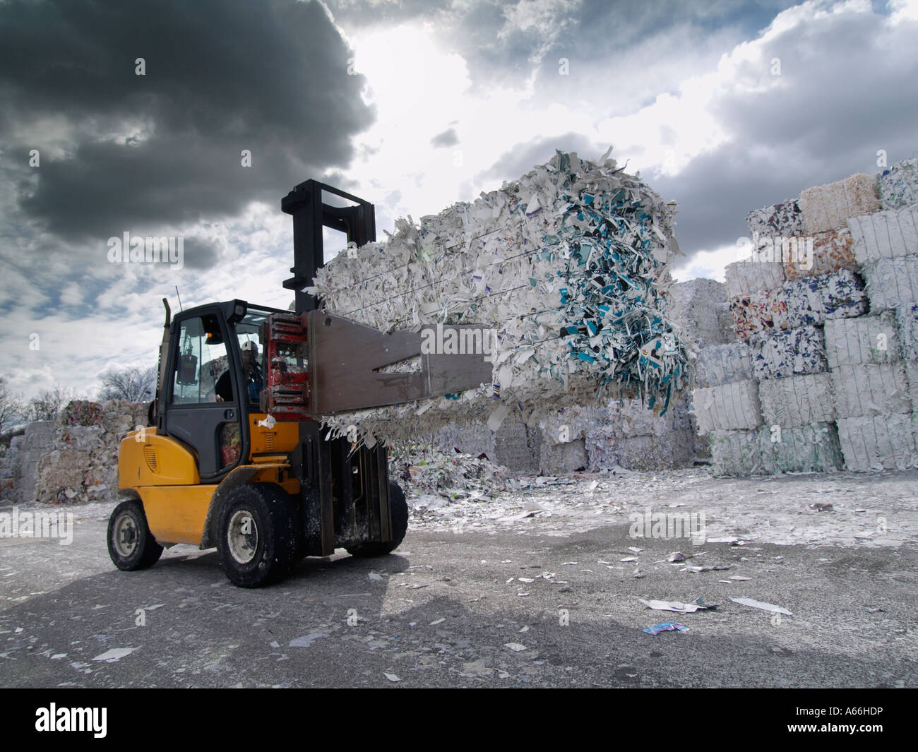 Forklift truck with clamping grip lifting a large bale of old used paper at a paper recycling factory in Cuijk the - Stock Image