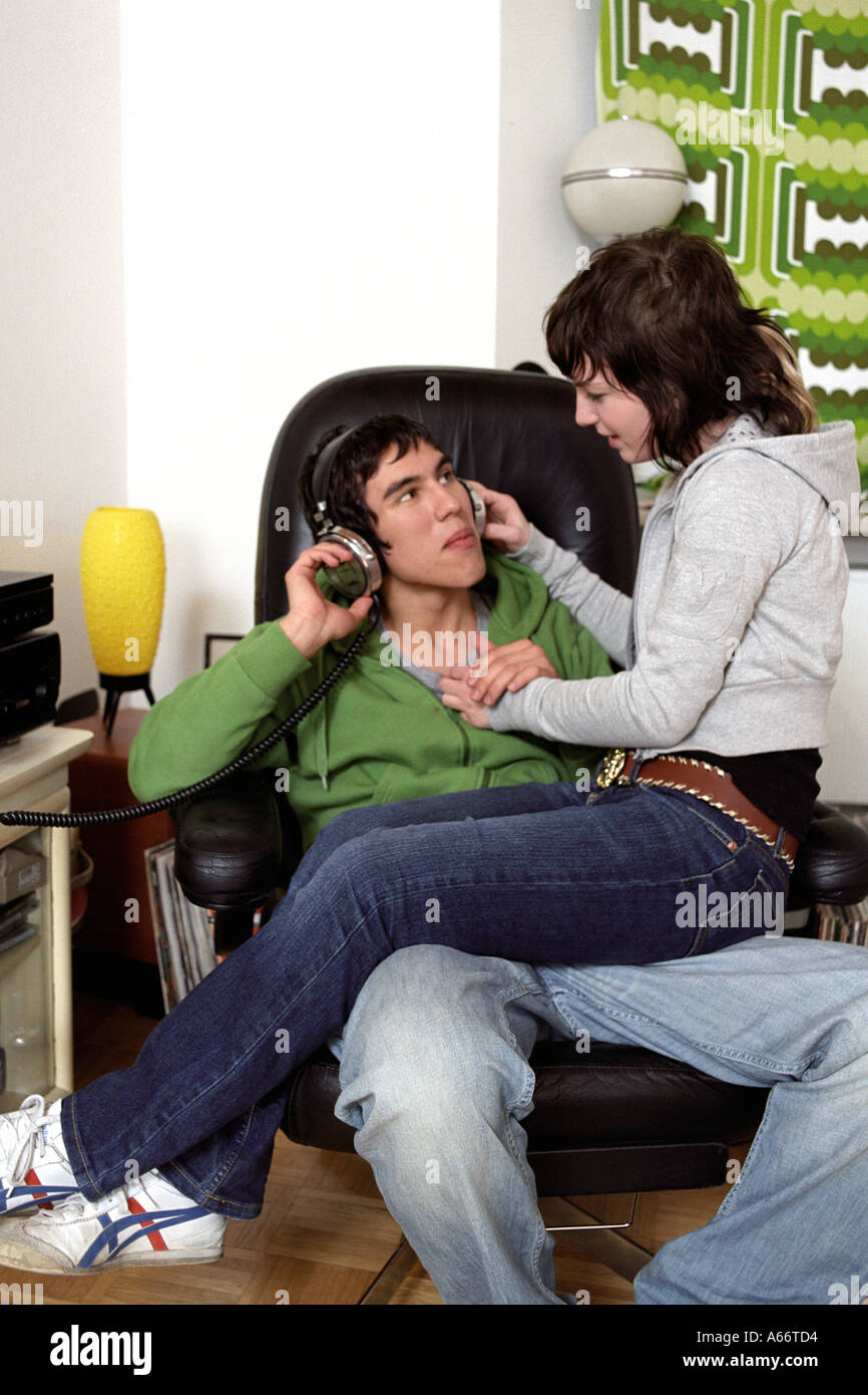 Teenage Girl Sitting On Lap Of Boyfriend Who Is Listening To Music Stock Photo Alamy
