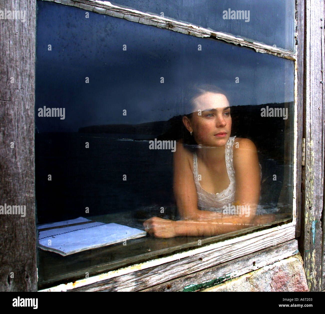 A young woman looks out a window of an isolated hut. - Stock Image