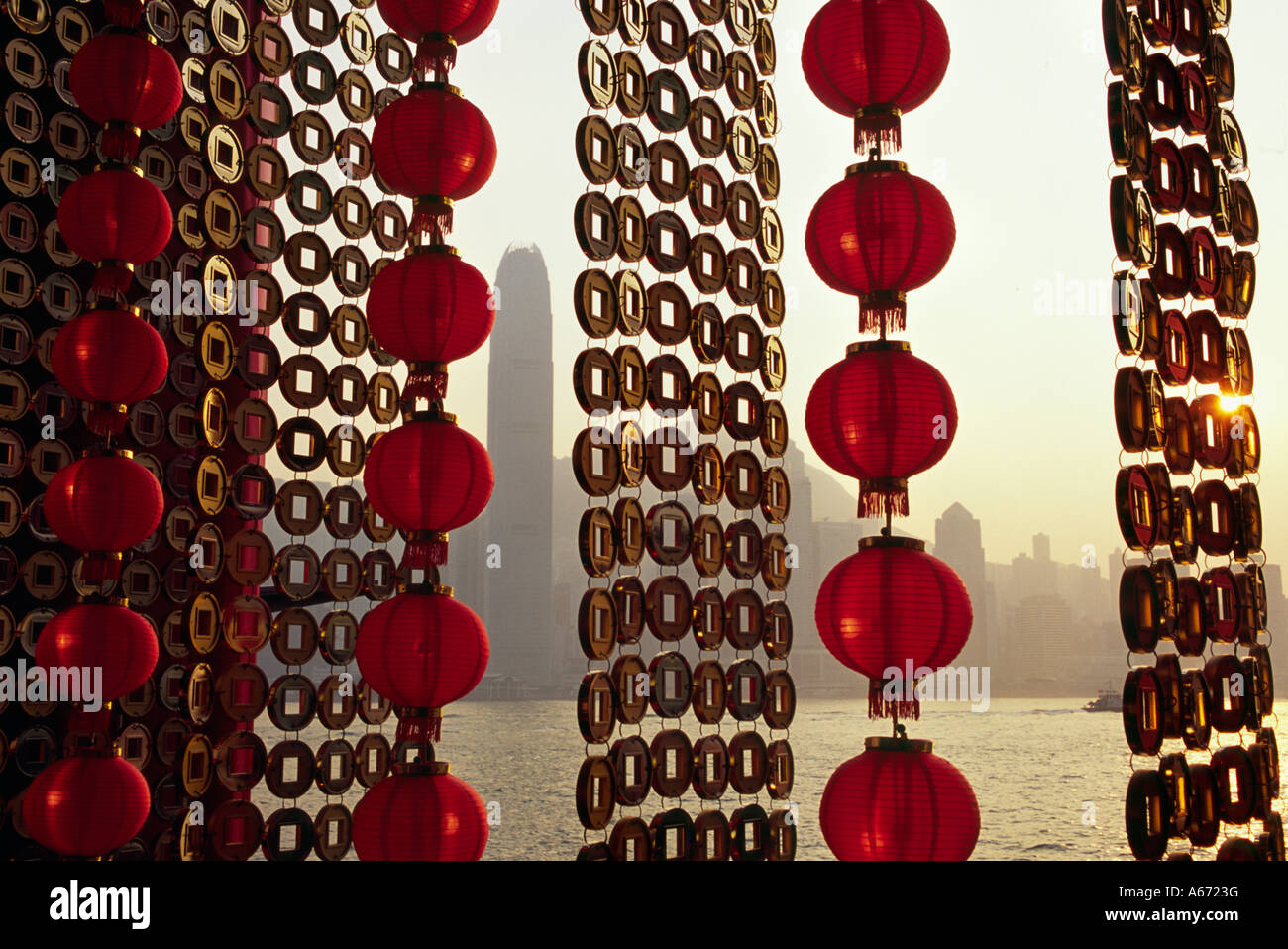 A curtain of Chinese New Year decorations frame a view of Victoria Harbour from Tsim Sha Tsui in Hong Kong Stock Photo