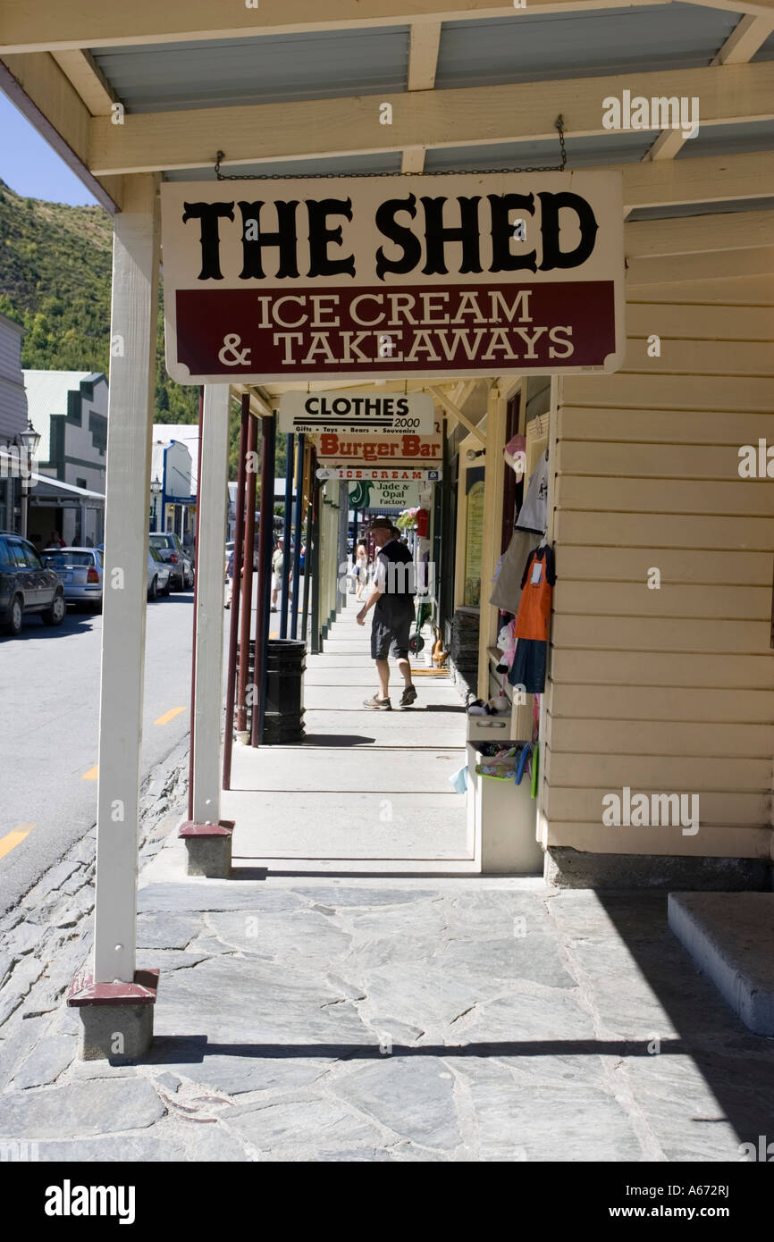 Signboards hanging from old timber buildings now shops in main street historic former goldrush town of Arrowtown - Stock Image