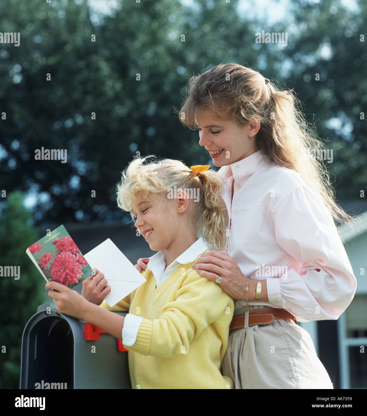 Mother and daughter at mailbox reading a greeting card - Stock Image