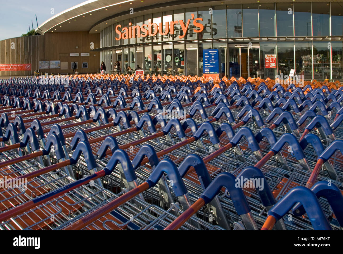 Large concentration of Sainsburys supermarket trolleys in front of store entrance - Stock Image