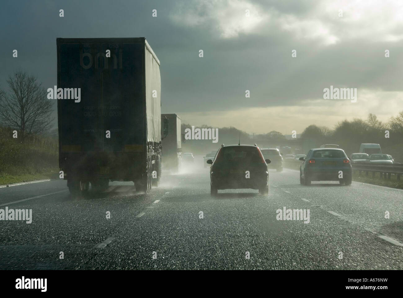 Winter motorway driving towards low sun after heavy rain shower poor visibility from spray - Stock Image