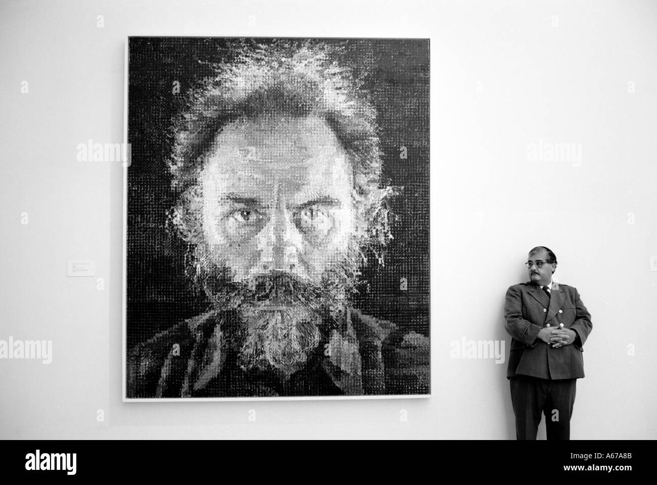 Art Chuck Close painting with museum guard standing next at the Metropolitan Museum Of Art New York City - Stock Image