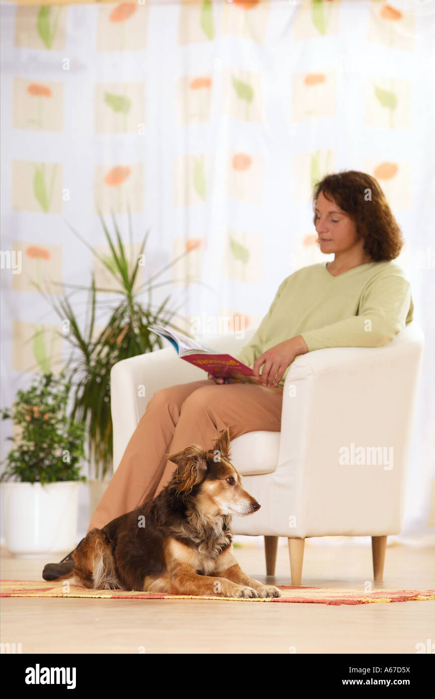 woman reading a book - half breed dog sitting besides her - Stock Image