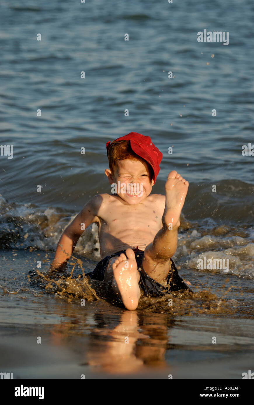 Little boy sits on the beach and splashes with water - Stock Image