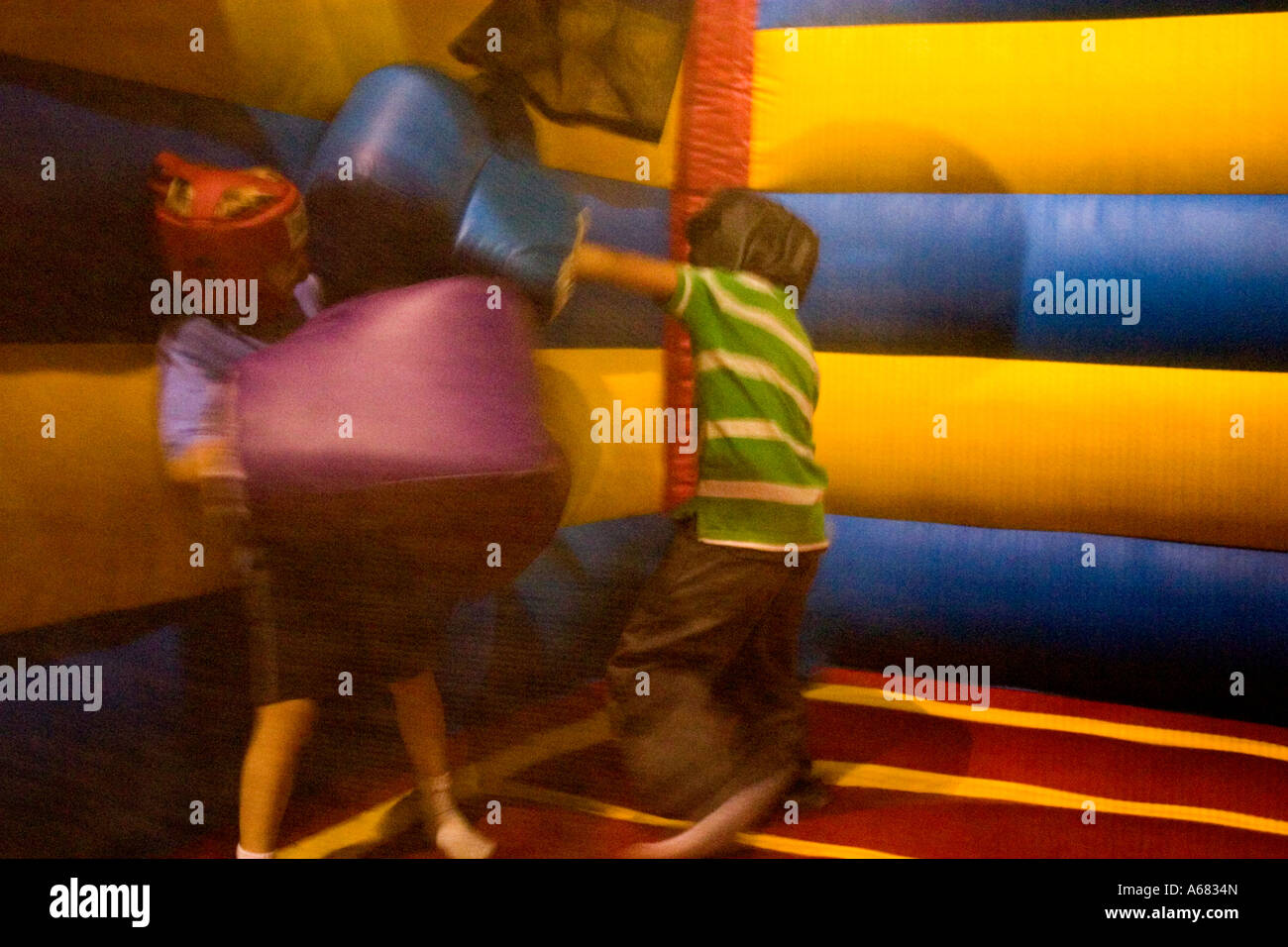 Boys age 7 boxing at Pump It Up - The Inflatable Party Zone - indoor entertainment for children.  Burnsville Minnesota - Stock Image