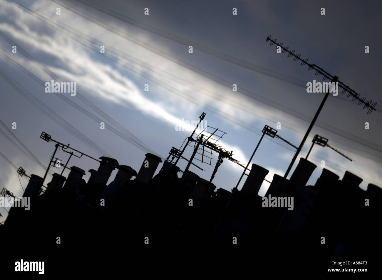 A roofscape with chimney pots and tv aerials at dusk  in a quiet Victorian terraced back street in the city of Brighton and Hove - Stock Image