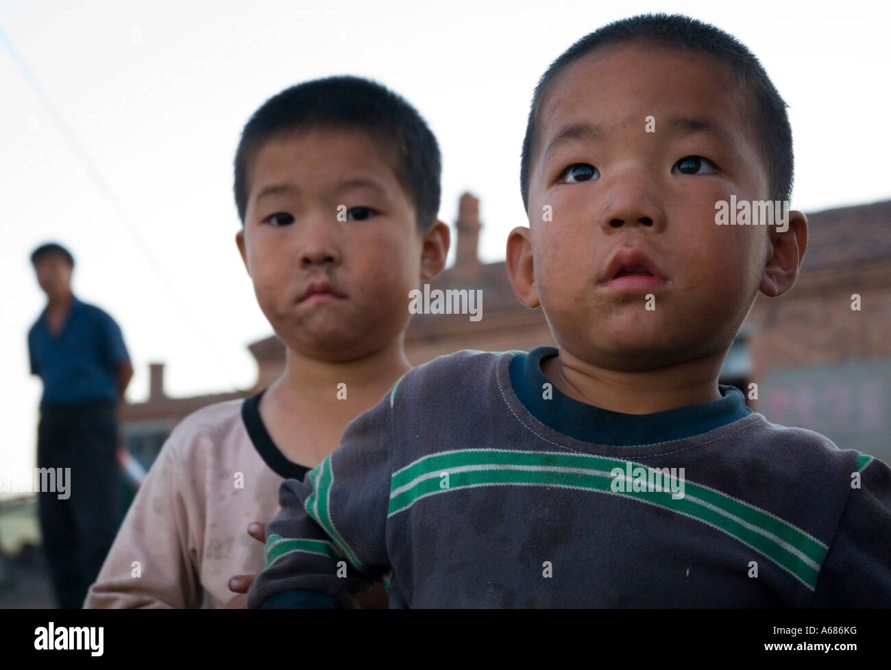 At a small coal mine in the province of Inner Mongolia in China children play while their parents work - Stock Image