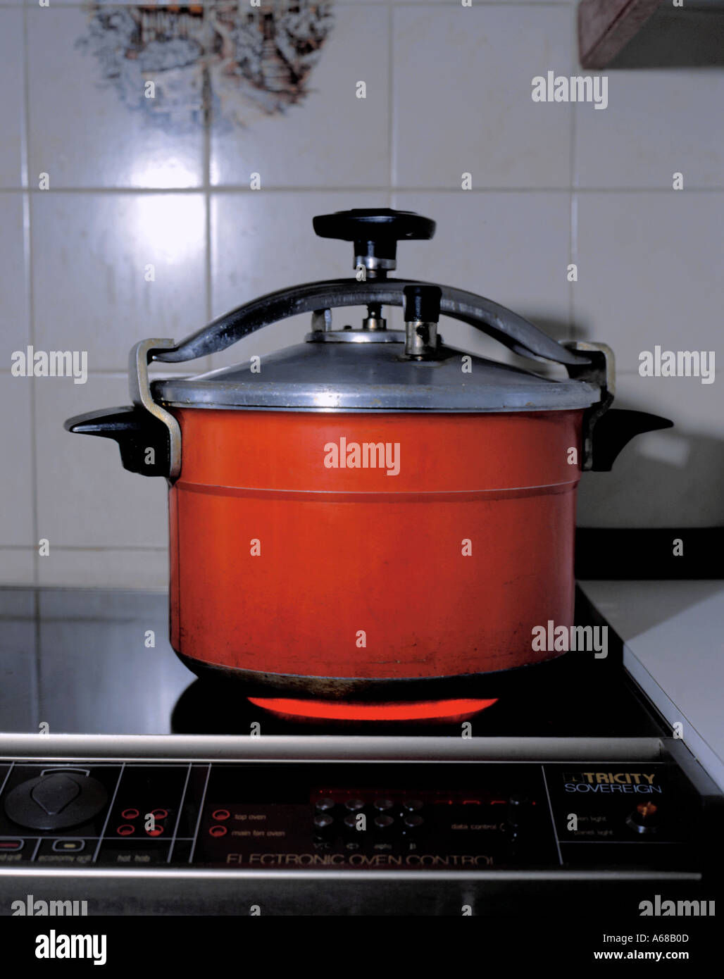 Anodised aluminium pressure cooker on a halogen hob. - Stock Image