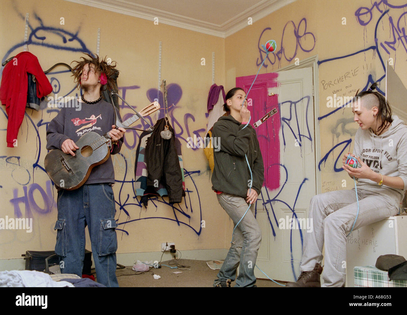 Group of teenaged boys and girls fooling around playing instruments in their room in south London squat. - Stock Image