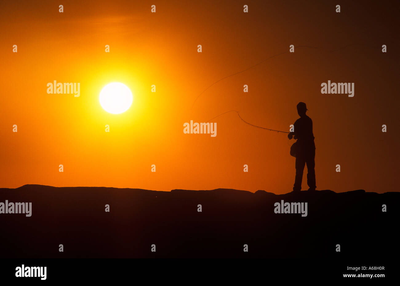 Boy fishing from a jetty at sunset Menemsha Marthas Vineyard - Stock Image
