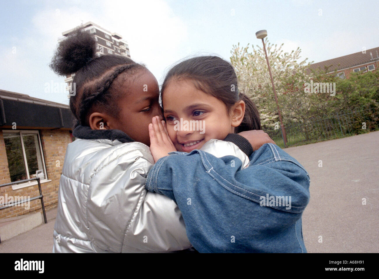 Two girls whispering a secret to each other at break time in primary school. - Stock Image