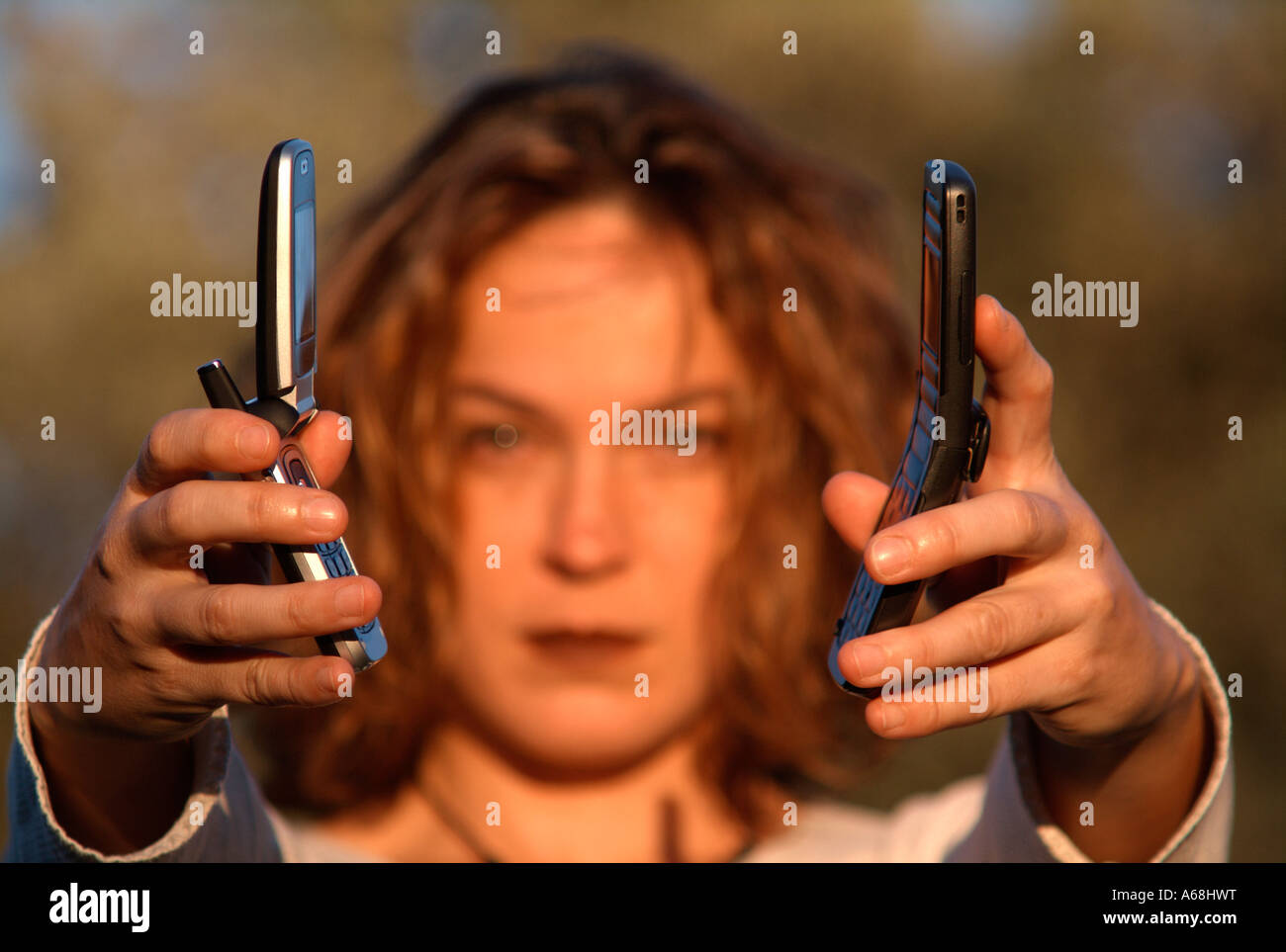 Young girl showing two cellular phones in outdoors, with sunset light. Stock Photo