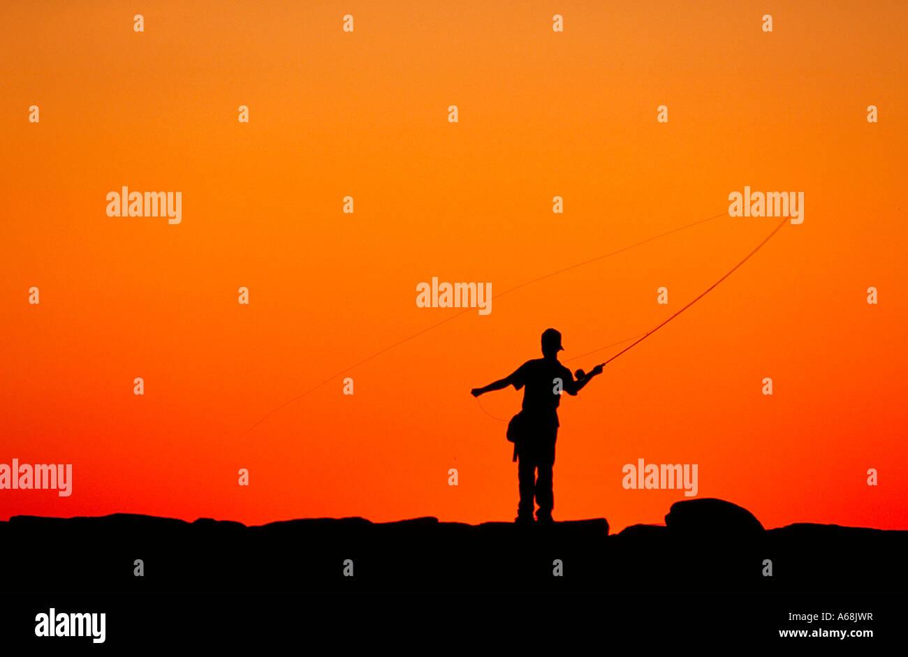 Boy fishing from a jetty at sunset Menemsha Martha s Vineyard - Stock Image