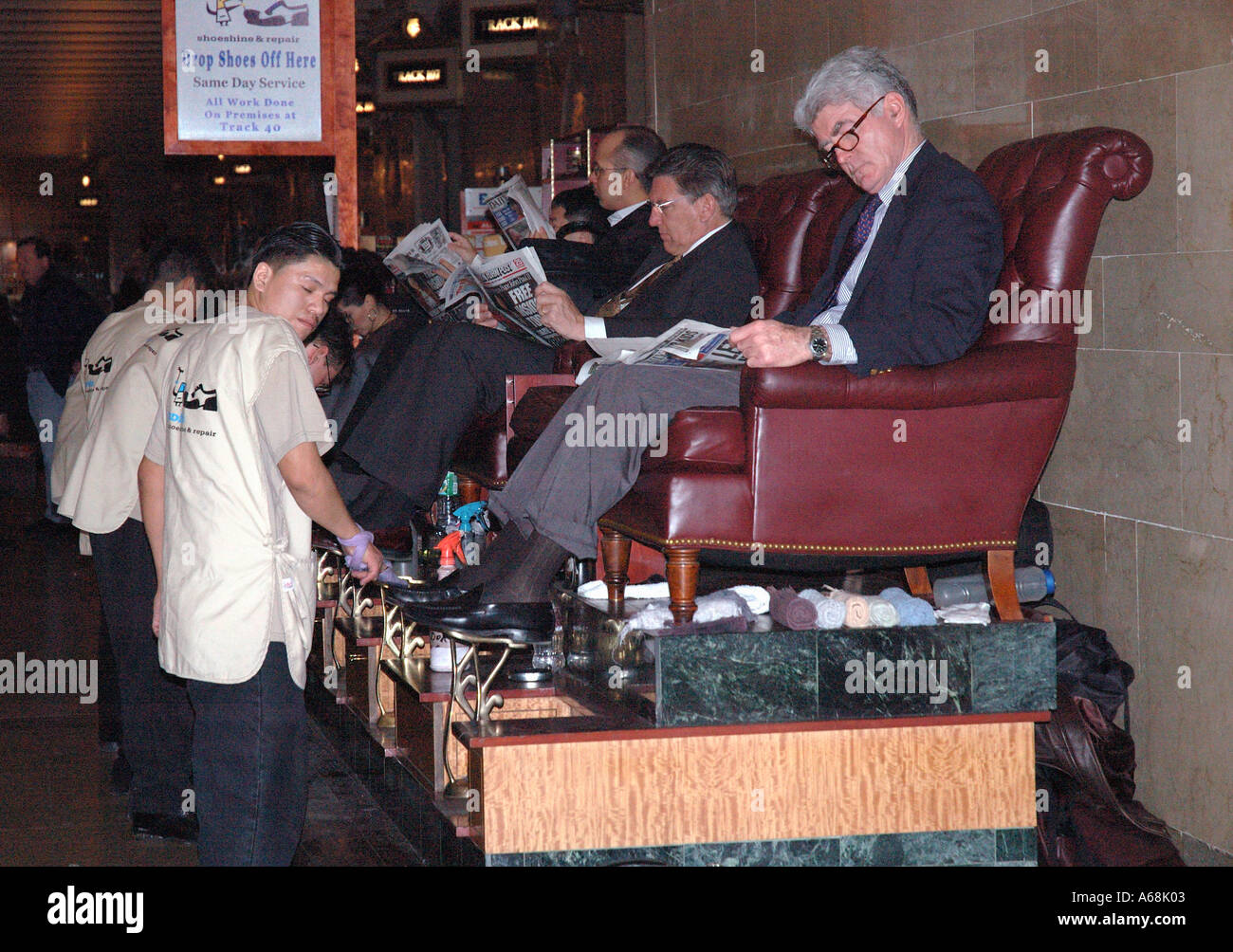 Young boys shoe cleaning and shining at Grand Central Station cleaning business means shoes. - Stock Image