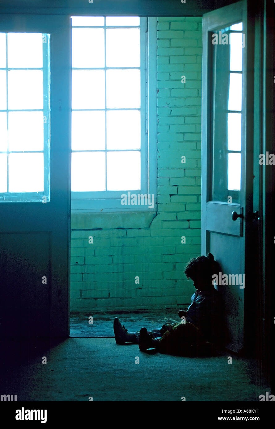 Small child sits alone in the dark dirty hallway of a rundown apartment building - Stock Image