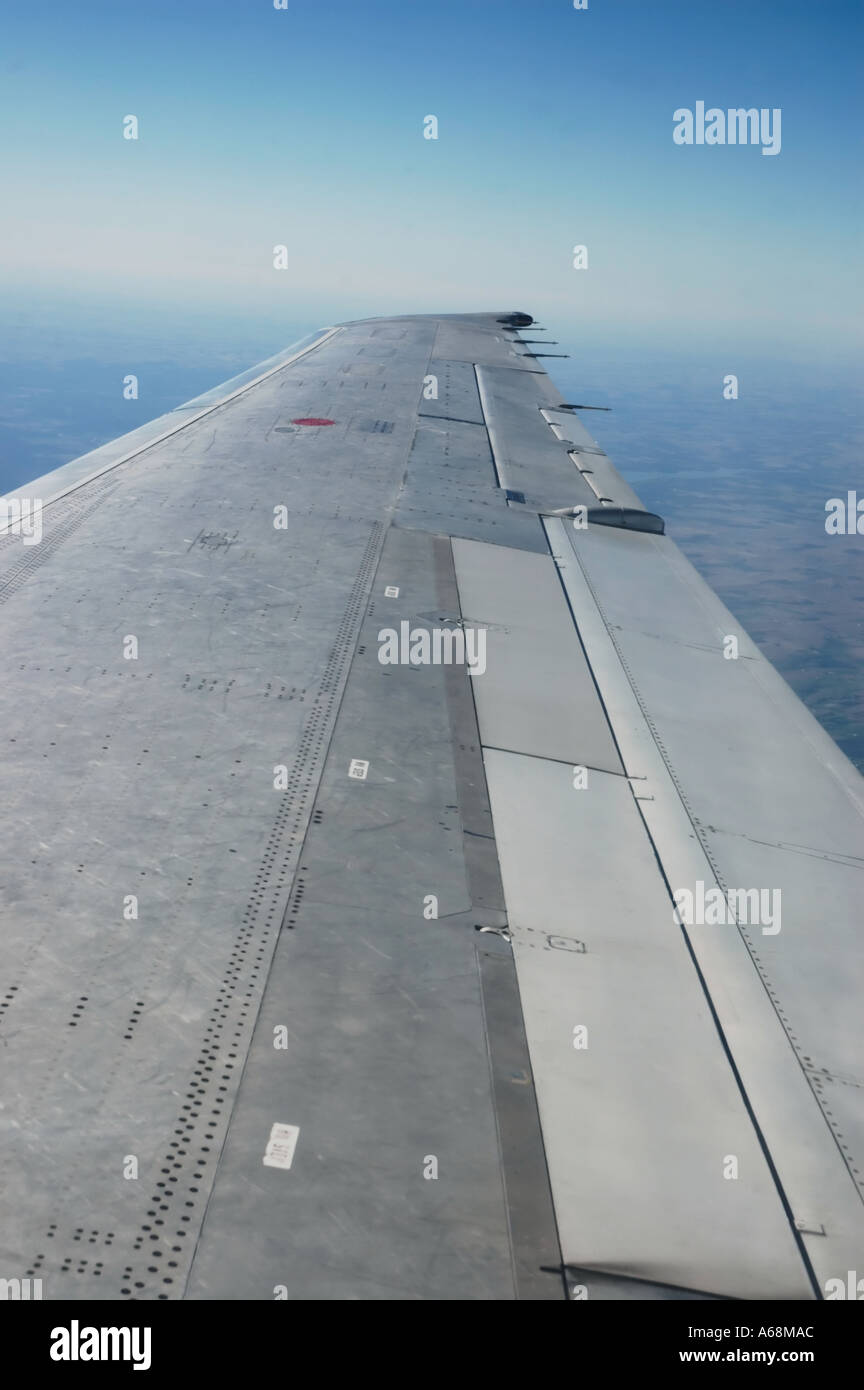 View of the airplane wing of a commercial airliner in flight - Stock Image