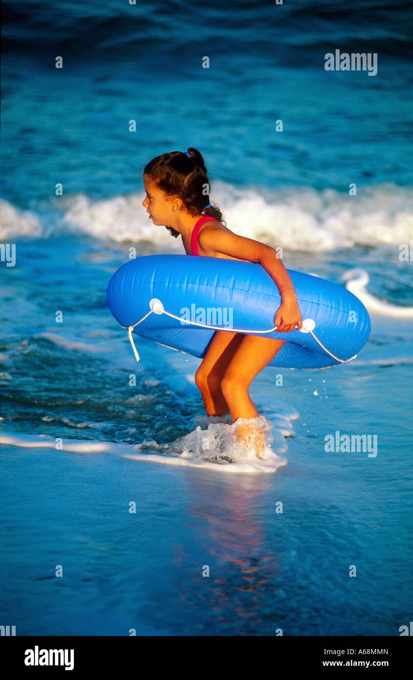 A young girl plays with an inner tube on the beach as waves wash in to shore - Stock Image
