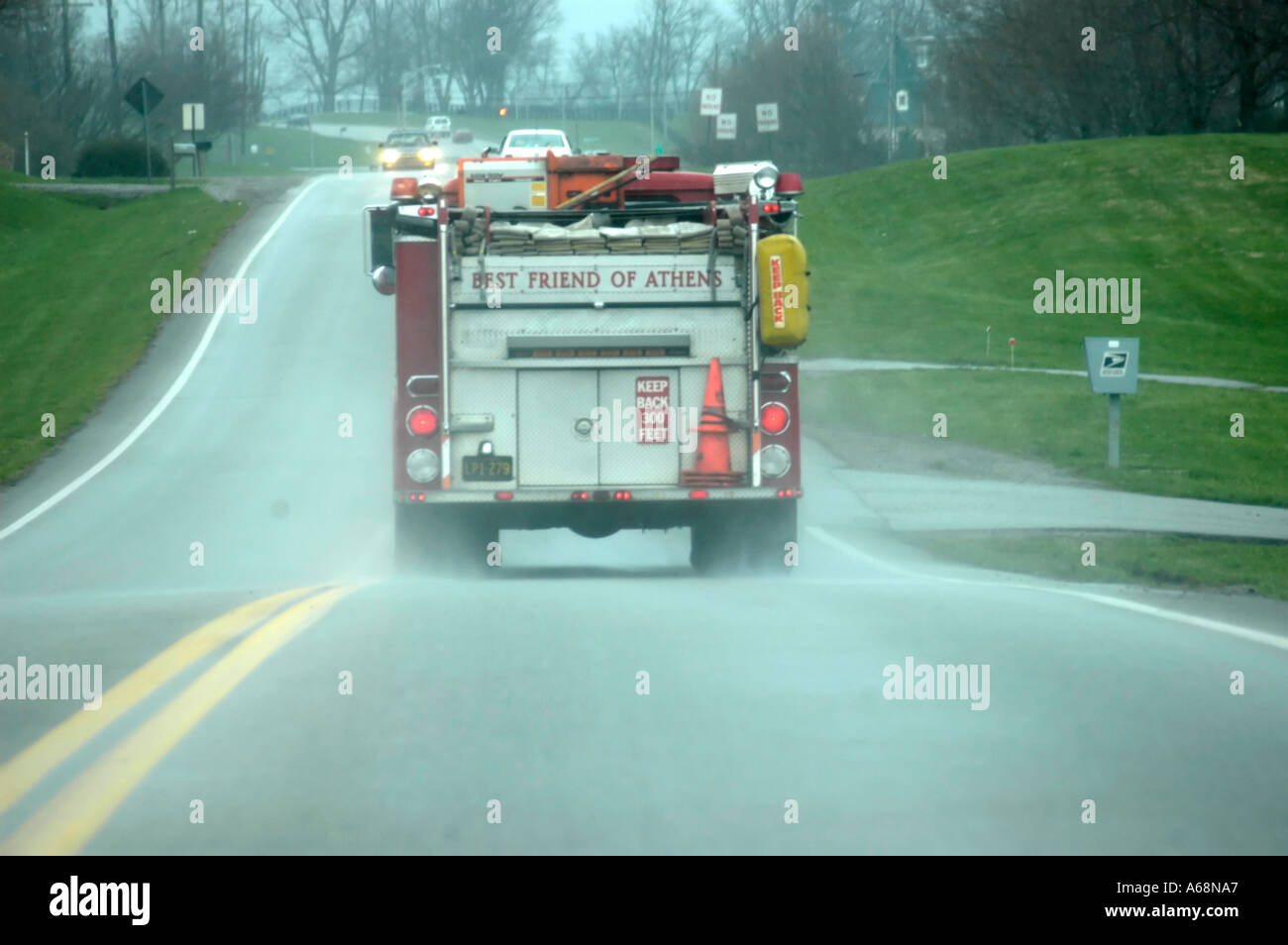 Rear view of a red fire truck speeding down a rain slicked road in the Bluegrass region of Kentucky USA Stock Photo