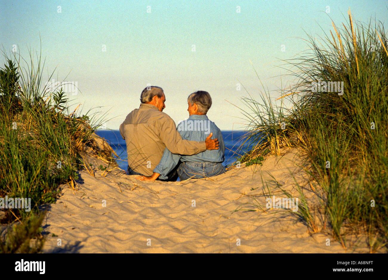 Senior couple enjoy ocean sunset while relaxing on sand dune - Stock Image