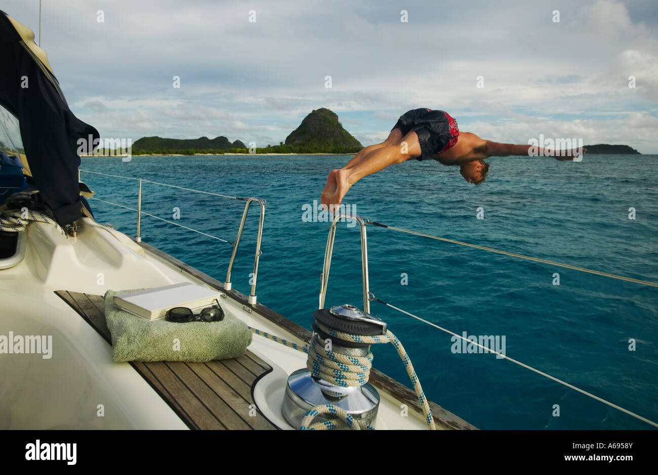 Man diving from  sailboat in the Grenadines of the Winward Islands British West Indies Stock Photo