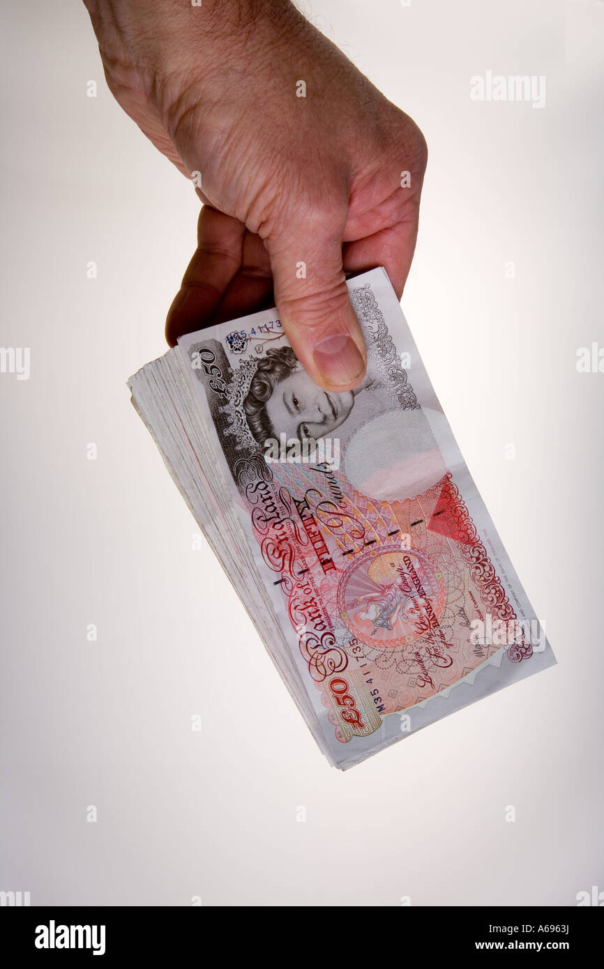 Hand holding fan of twenty 50 pound notes - Stock Image