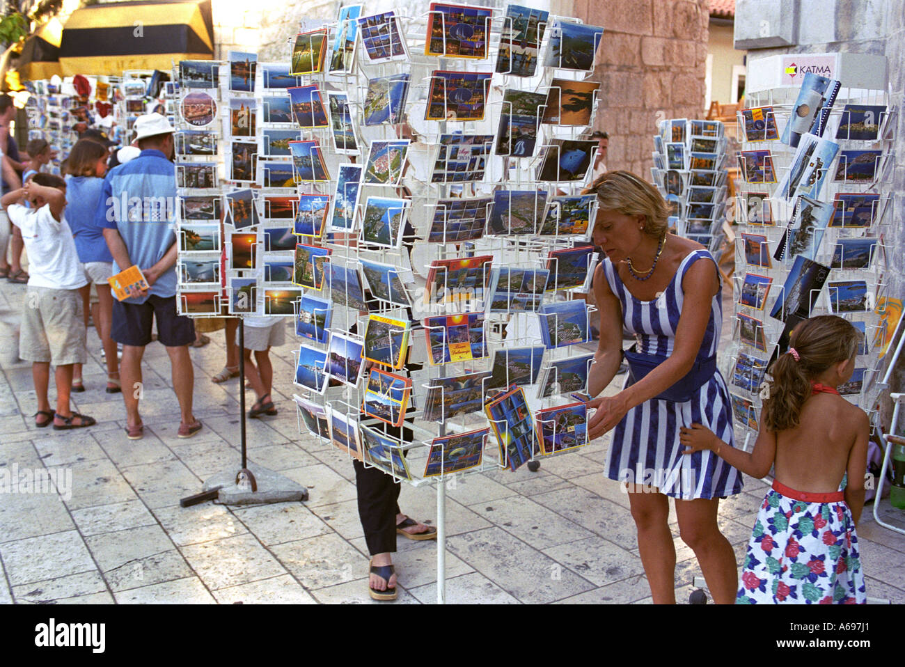Tourists look at the postcards displayed in the seaside holiday resort Trogir - Stock Image