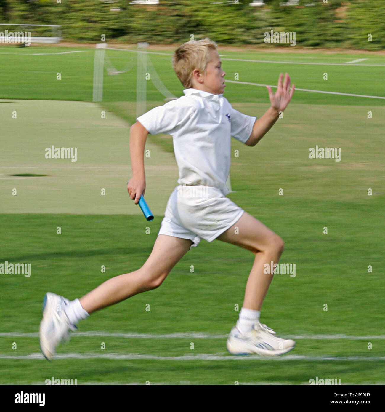 Boy sprinting in school sports day relay race - Stock Image