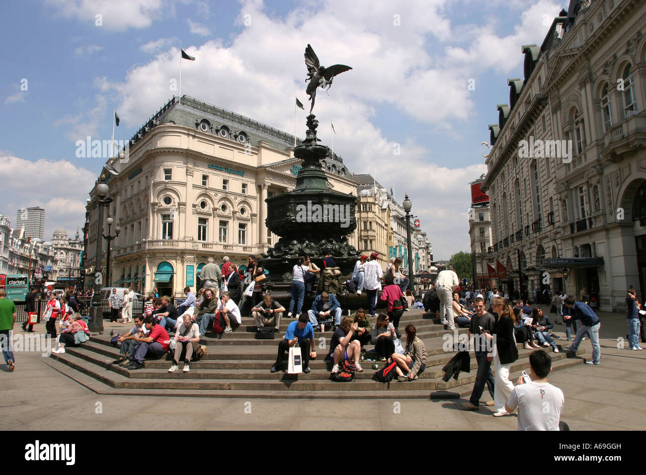 UK London Piccadilly Circus tourists sat beneath statue of Eros - Stock Image