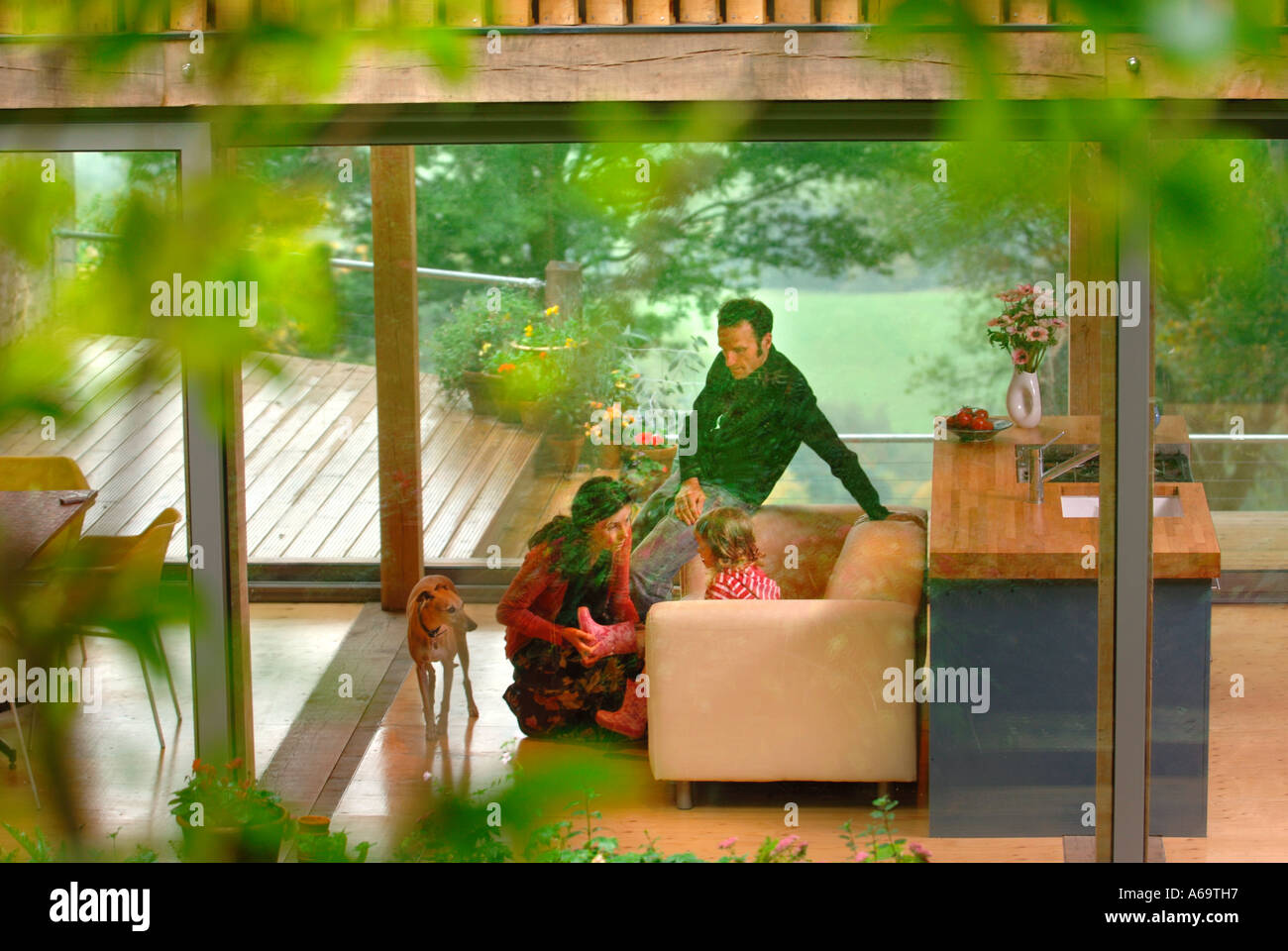 A YOUNG FAMILY IN A MODERN HOUSE WITH LARGE GLASS SLIDING WINDOWS UK - Stock Image