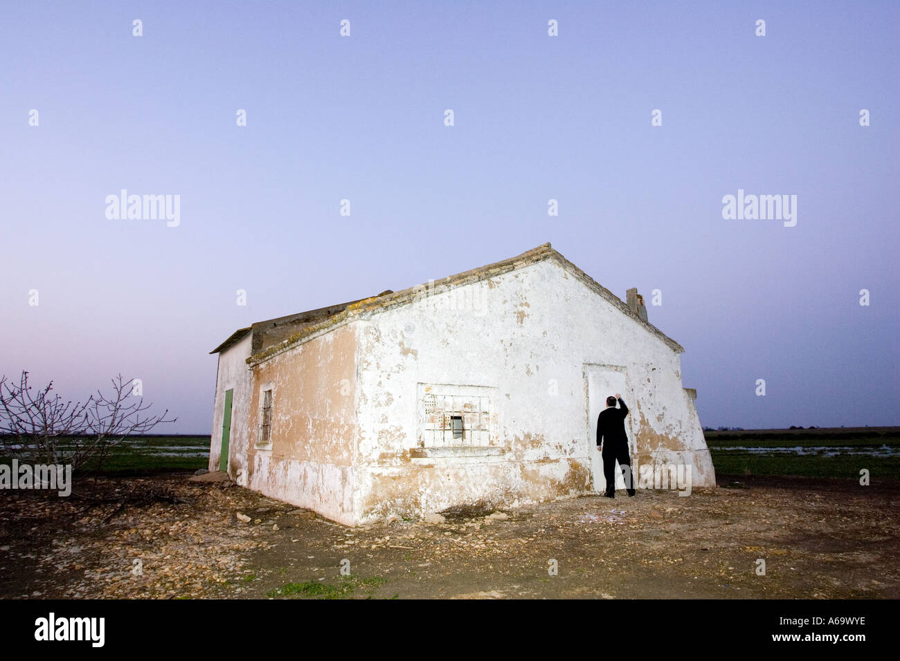 Man knocking on an abandoned house blocked off door at dusk. image conveys a sense of loneliness, despair and desolation. - Stock Image
