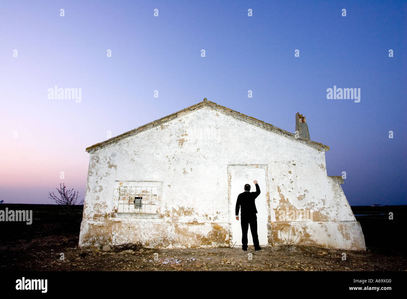 Man knocking on an abandoned house blocked off door at dusk. image conveys a sense of loneliness, despair and desolation - Stock Image